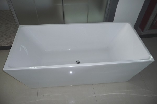 Freestanding rectangular bathtub is displayed in the showroom
